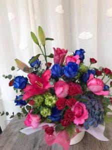青いバラを入れた明るいお祝いのアレンジ